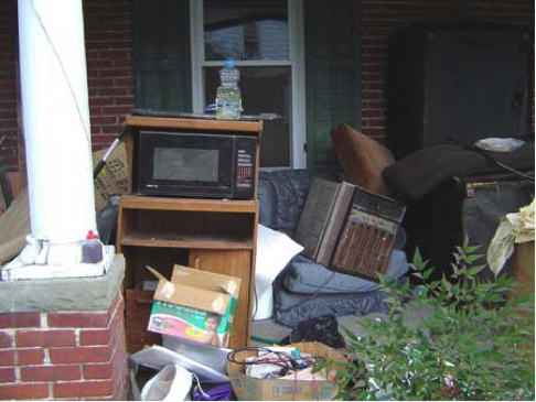 Trash a furniture piled in houses' front porch