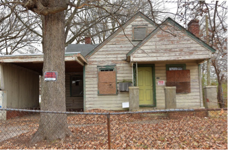 abandoned, boarded-up house in deteriorated condition