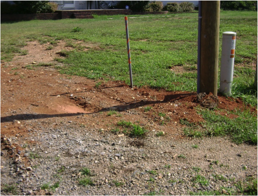 image of outdoor area around electric pole where the dirt has been dug up and paid back in a relatively flat manner, with some tire treads showing, and minimal loss of grass cover