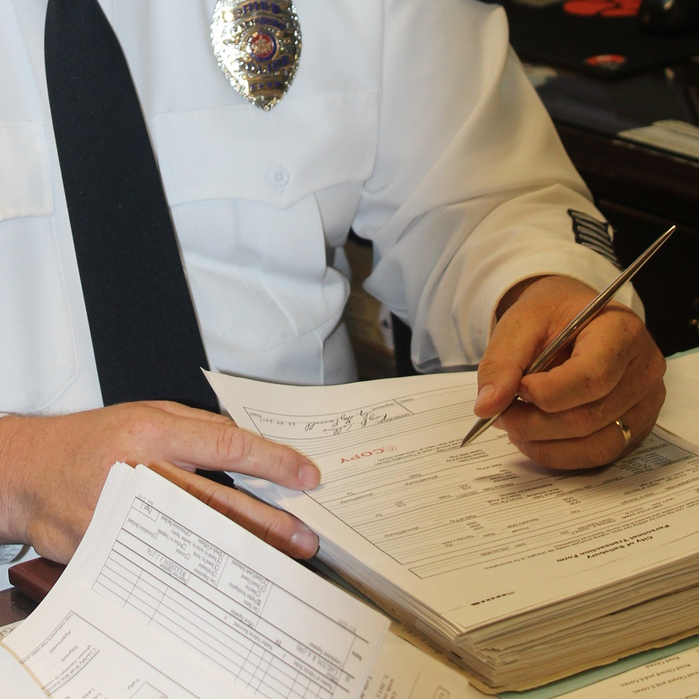 the police chief working on paperwork in his office