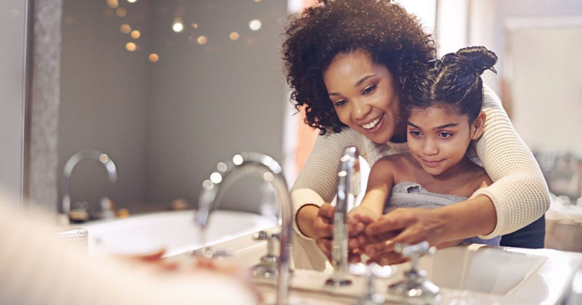 woman with daughter washing hands in bathroom sink