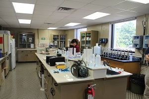 the water testing lab, with staff checking a fluid mix inside a glass beaker