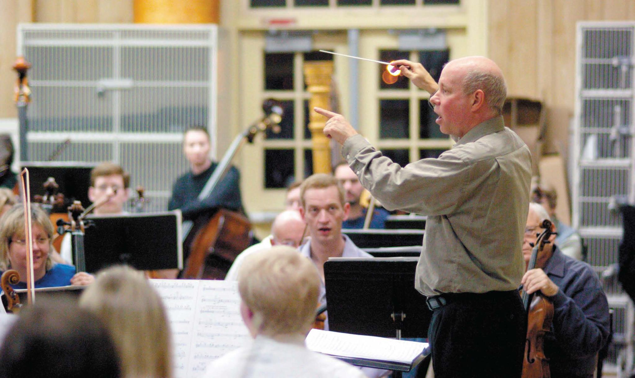 The conductor leading the symphony during a concert